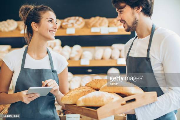 Smiling bakers with digital tablet and bread tray