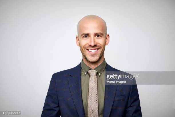 smiling bald businessman wearing navy blue suit - businessman stock pictures, royalty-free photos & images