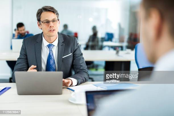 smiling bank manager talking to his customer in the office. - bank manager stock pictures, royalty-free photos & images