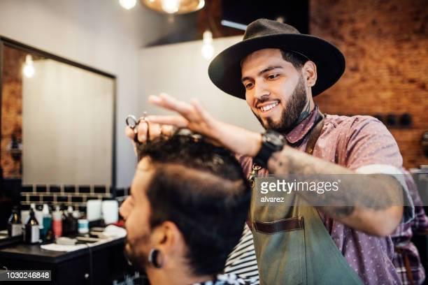 cheveux du client souriant coiffeur coupe au salon - salon de coiffure photos et images de collection