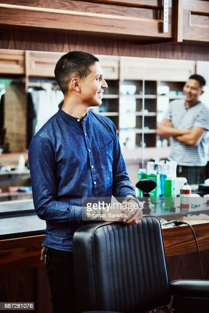 Smiling barber in discussion with client in barber shop