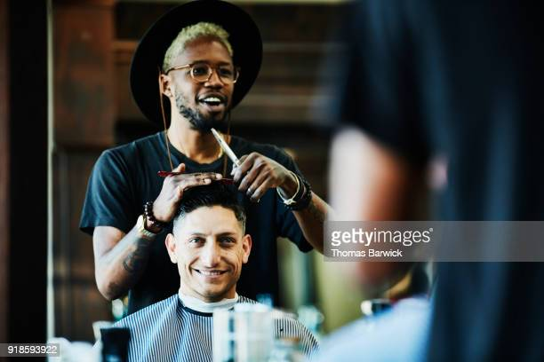 smiling barber in discussion with client while cutting hair in barber shop - barber stock pictures, royalty-free photos & images