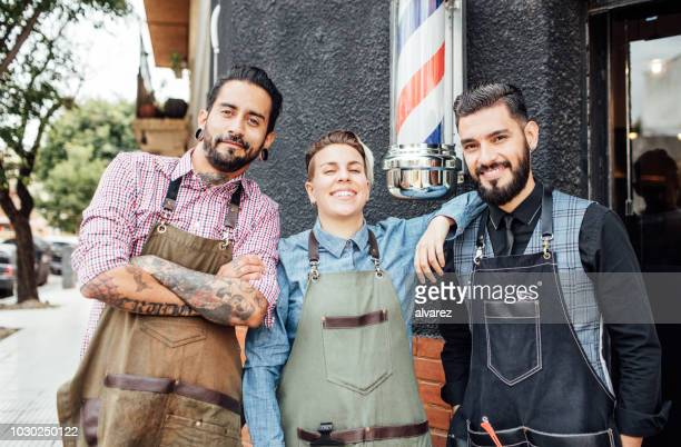 smiling barbers standing outside hair salon - barber pole stock photos and pictures