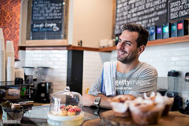 Smiling barista at coffee shop counter