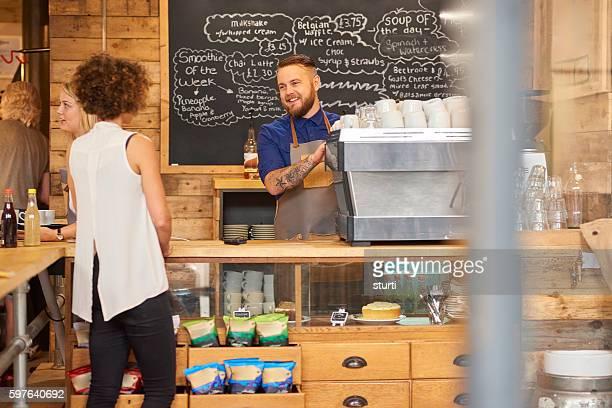 Smiling barista serving customer
