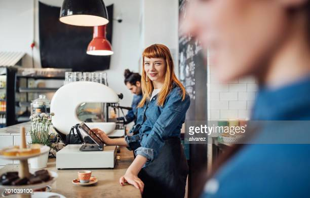 Smiling barista standing at counter in cafe