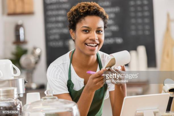 Smiling barista takes order in coffee shop
