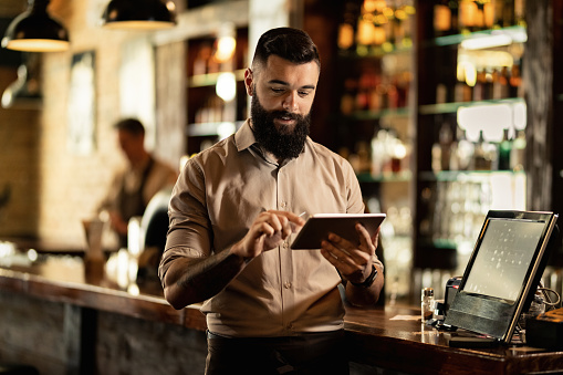 Smiling barista using digital tablet while working in a bar. 1212064164
