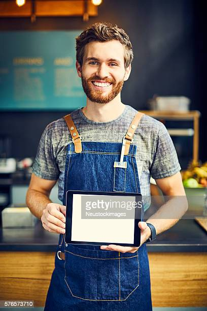 Smiling barista with blank digital tablet