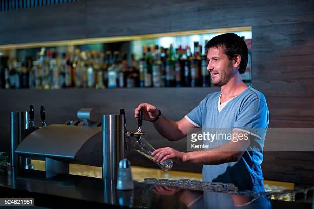 Lächeln barkeeper füllen ein Glas mit Bier