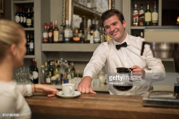 Smiling barkeeper preparing cup of coffee for woman