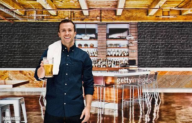 Smiling bartender holding glass in bar