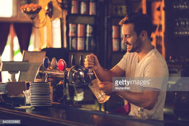 Smiling bartender pouring beer from beer tap in a bar.