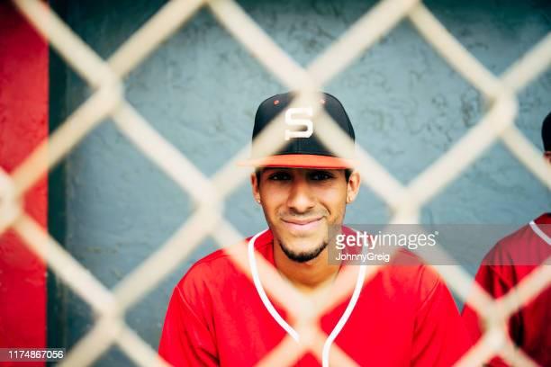 ダッグアウトフェンスを通して撮影された笑顔の野球選手 - 高校野球 ストックフォトと画像
