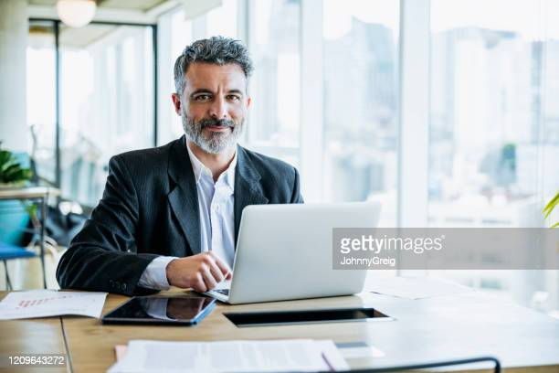 uomo d'affari barbuto sorridente che lavora su laptop in ufficio - professione foto e immagini stock