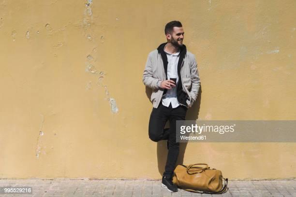 smiling bearded man with coffee to go, leaning on wall - bolsa preta - fotografias e filmes do acervo