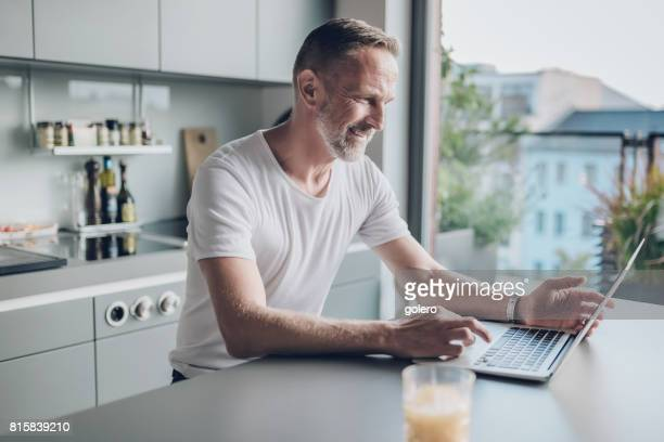 smiling bearded midaged man with laptop at kitchen table