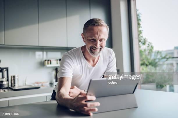 lächelnd, bärtiger midaged Mann mit Tablet am Küchentisch