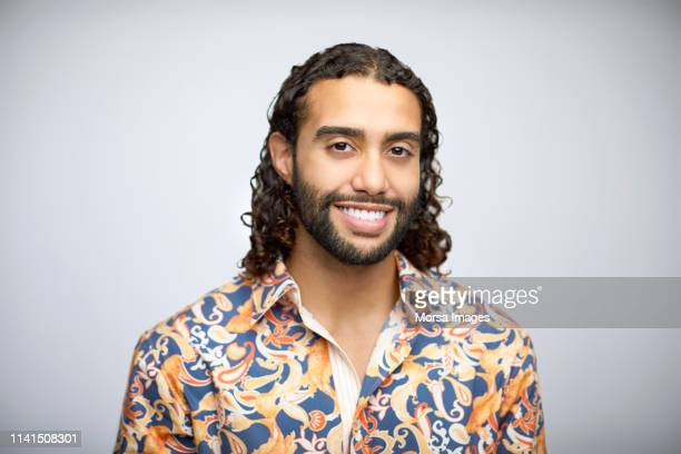 smiling bearded young man having long curly hair - long hair stock pictures, royalty-free photos & images