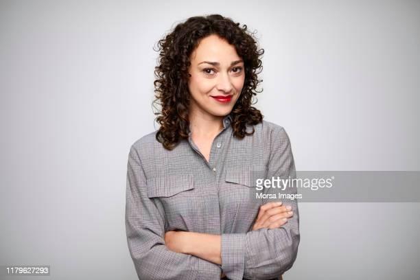 smiling beautiful female ceo with arms crossed - retrato formal imagens e fotografias de stock