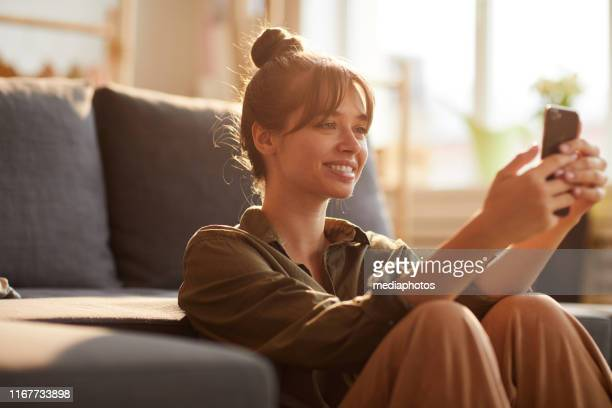 smiling beautiful girl with bangs leaning on sofa and browsing internet on smartphone while searching for information - social media marketing stock pictures, royalty-free photos & images