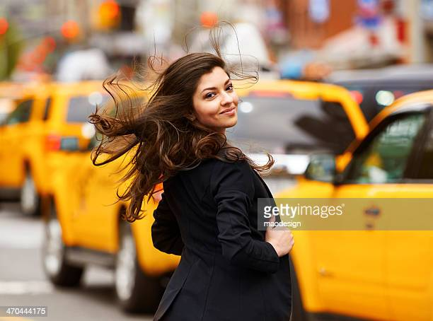 Smiling beautiful girl with dispelled hair walking on NY street