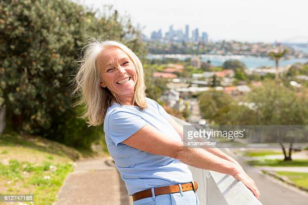 Smiling beautiful happy blond mature woman standing in sunshine