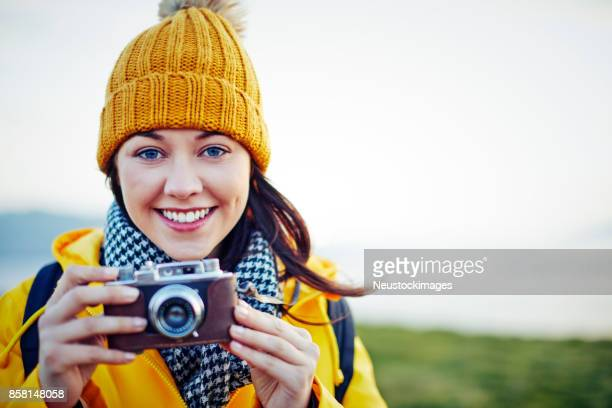 Smiling beautiful hiker holding vintage camera against clear sky