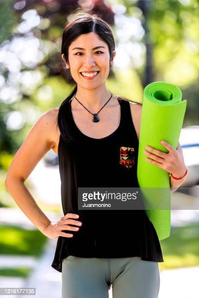 smiling beautiful mid adult asian woman looking at the camera on her way to her yoga class carrying a yoga mat - only japanese stock pictures, royalty-free photos & images