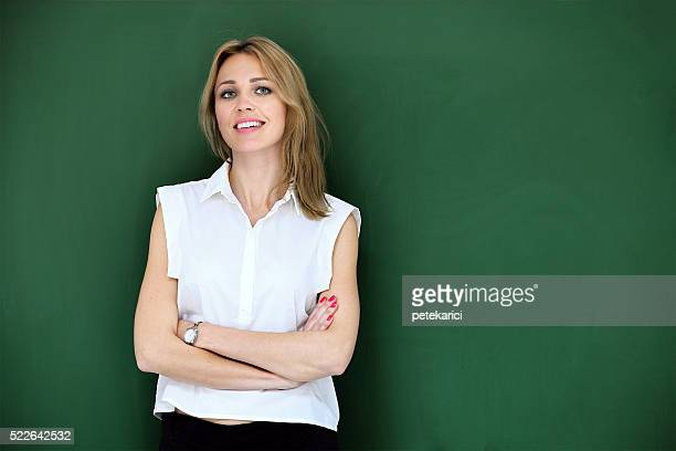 Smiling beautiful teacher at blackboard