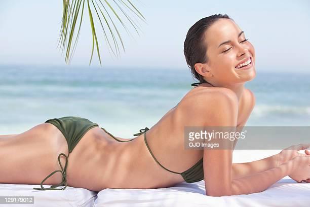 sonriendo hermosa adolescente acostado boca abajo en la playa - acostado boca abajo fotografías e imágenes de stock