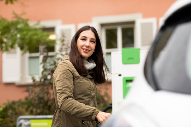 Smiling beautiful woman at electric vehicle renting station