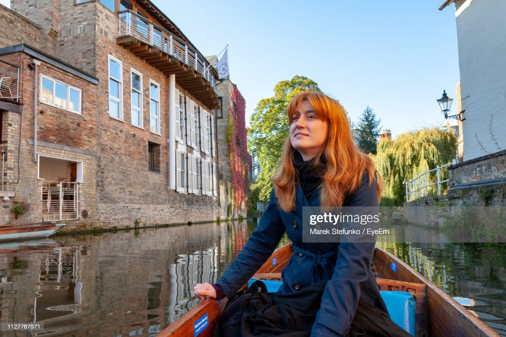 Smiling Beautiful Woman Boating On Canal Amidst Buildings : Stock Photo