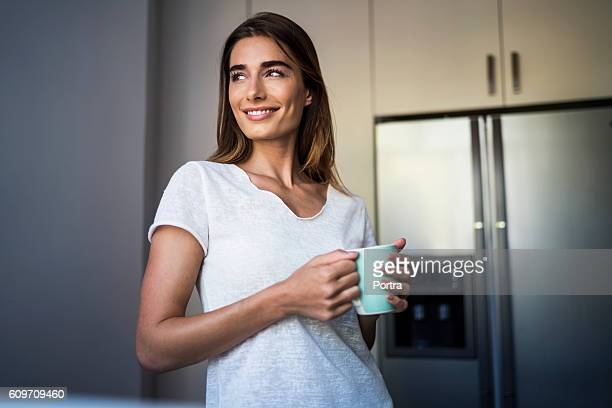 Smiling beautiful woman having coffee at home