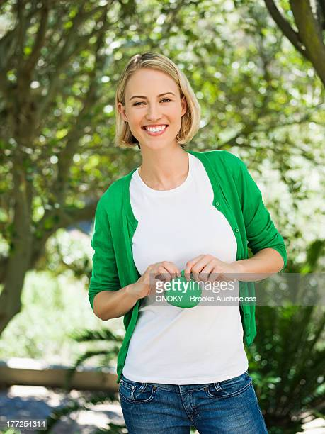 smiling beautiful woman holding a pouch bag - one mid adult woman only stock pictures, royalty-free photos & images