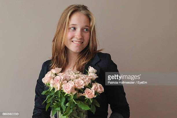 Smiling Beautiful Woman Holding Rose Bouquet Against Beige Background