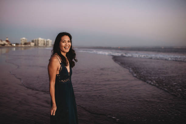 Smiling beautiful woman in long dress wading into the ocean surf