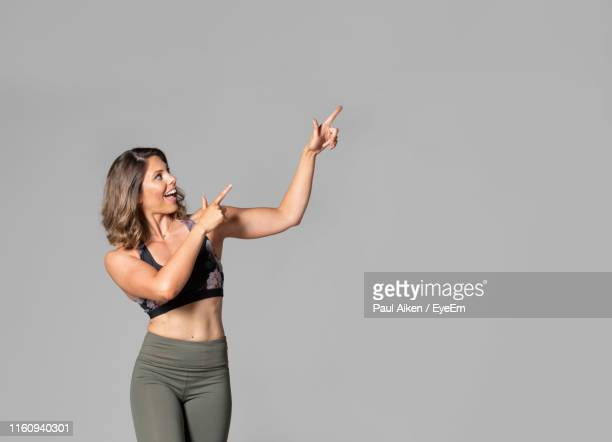 smiling beautiful woman pointing while standing against gray background - aikāne stock pictures, royalty-free photos & images
