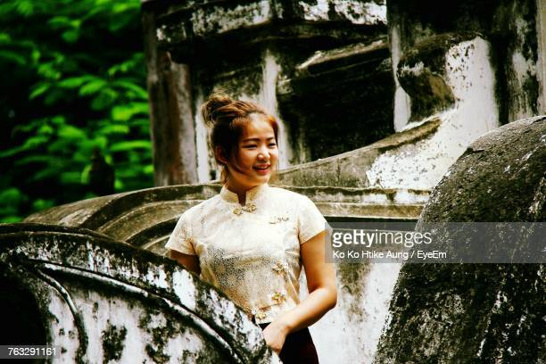 smiling beautiful woman standing at abandoned building - ko ko htike aung stock pictures, royalty-free photos & images