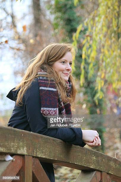Smiling Beautiful Woman Standing By Wooden Railing In Park During Autumn