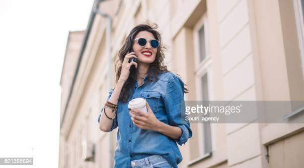 lächelnde schöne frau telefonieren mit dem handy - jeansstoff stock-fotos und bilder