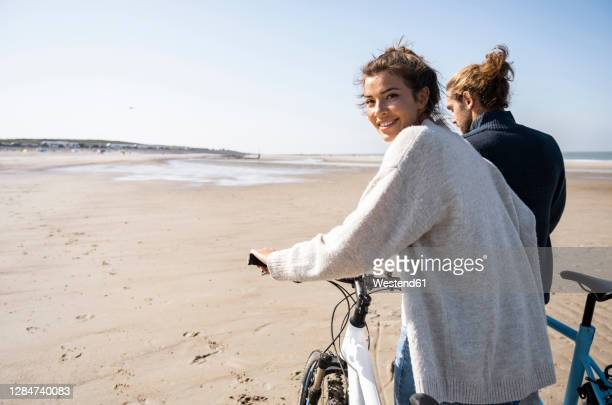 smiling beautiful woman walking with bicycle by boyfriend while looking over shoulder at beach against clear sky on sunny day - netherlands stock pictures, royalty-free photos & images