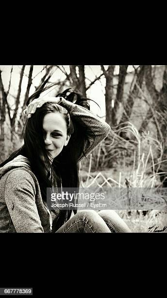 smiling beautiful woman with hand in hair sitting against trees - transferbild stock-fotos und bilder