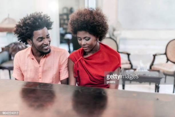 lächelnde schöne junge kubanische paar Klavier zu spielen