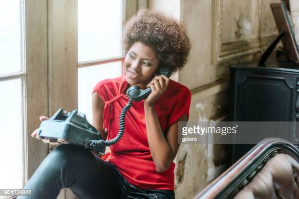 smiling beautiful young cuban woman sitting on sofa talking at old phone