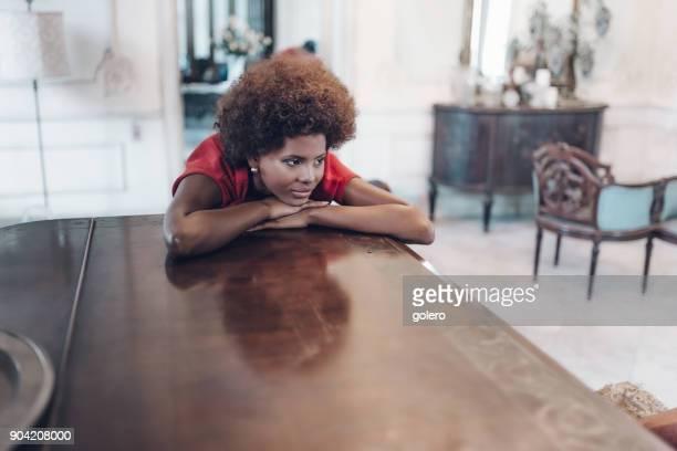 lächelnde schöne junge kubanische Frau dich am Fenster