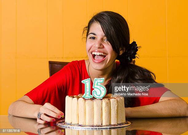 Smiling beautiful young fifteen year old girl in red dresscelebrating her birthday blowing candles on cake indoor Birthday party for teenagers