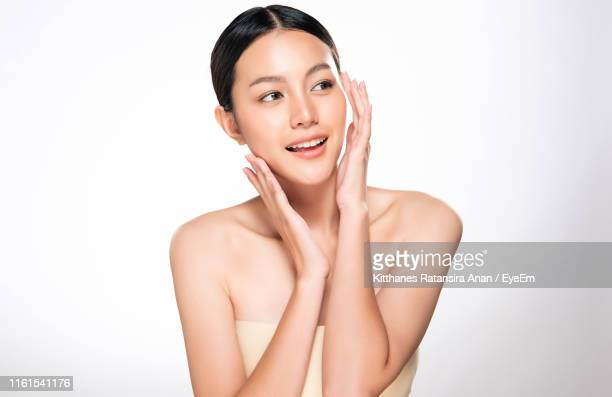 smiling beautiful young woman looking away against white background - 人の肌 ストックフォトと画像