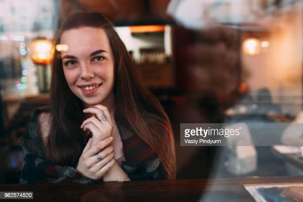 Smiling beautiful young woman seen through cafe window