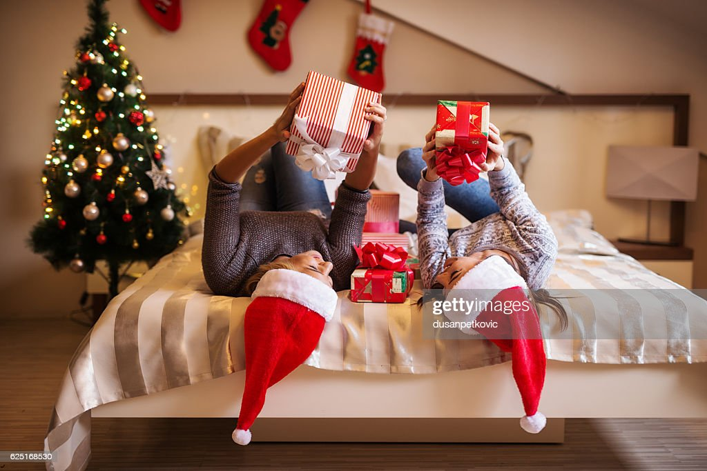 Smiling Beautiful Young Women Lying On Bed With Christmas Gift Stock ...
